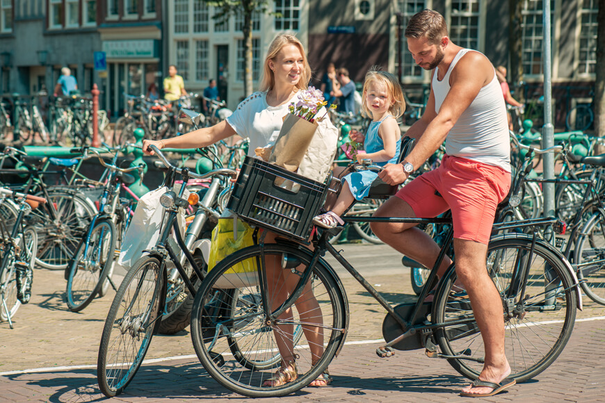 Young parents cycle with little daughter in child seat at Amsterdam streets